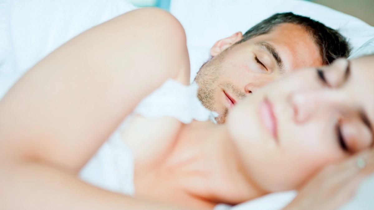 Muž a žena si užívají zdravý spánek v posteli.